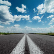 Two white lines on black road and dramatic sky with clouds over — Stok fotoğraf #50799159