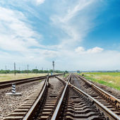 Crossing of railroad under cloudy sky — Stock Photo