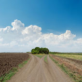 Two rural roads to horizon and clouds in blue sky — Stockfoto