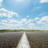 White line on asphalt road under sky with sun and clouds — Stock Photo