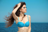 Beautiful woman sunbathing at the seaside over blue sky — Stock Photo