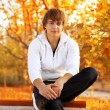 Young man sitting on the bench, autumn — Stock Photo