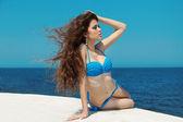 Hermosa joven con pelo largo y rizado en cielo azul — Foto de Stock