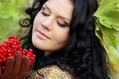 Portrait of beautiful Brunette Woman on green leaves with berry — Stock Photo