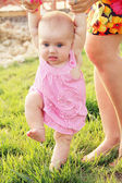 Baby learning to walk with help and support of mother's hands. F — Stockfoto
