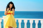 Young beautiful pregnant woman in dress over blue sky, ocean — Stock Photo