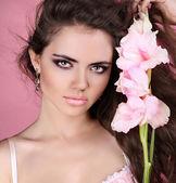 Jonge mooie vrouw met witte bloem over roze — Stockfoto