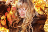 Beautiful blond middle aged woman in autumn leaves — Stock Photo