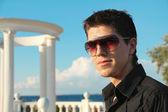 Porträt des jungen mann mit sonnenbrille lachen über blauer himmel — Stockfoto