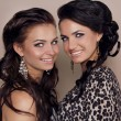 Two attractive smiling girls friends, sisters women studio shot — Stock Photo