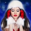 Santa girl listening to the music on blue background — Stock Photo