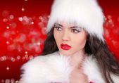 Santa girl with red lips looking away on red bokeh abstract — Stock Photo