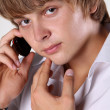 Close up of young handsome man talking on mobile phone against w — Stock Photo #13193452