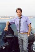 Homem de negócios jovem bonito relaxado perto do carro, do lado de fora — Foto Stock