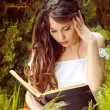 Young beautiful girl reading a book on green background of city — Stock Photo #13655837