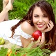 Happy Smiling Young Woman Eating Apple in the Orchard. Basket o — Stock Photo
