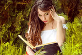 Young beautiful girl reading a book on green background of city — Stock Photo