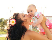 Happy mother kissing baby, outdoors portrait — Stock Photo