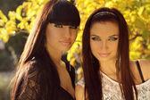 Two brunette women outdoors portrait. Soft sunny colors. — Stock Photo