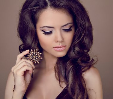 Beautiful woman with curly hair and evening make-up. Jewelry and