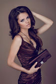 Fashion brunette woman in elegant dress with bag. Curly Hair sty — Stock Photo