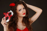 Beautiful Woman with red lips holding Carnival mask in hand. — Stockfoto