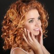 Attractive smiling girl with golden Curly Hair on dark backgroun — Stockfoto #17597647