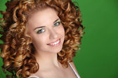 Curly Hair. Attractive smiling woman portrait on green backgroun — Foto de Stock