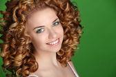 Pelo rizado. retrato de mujer sonriente atractivo en fondo verde — Foto de Stock