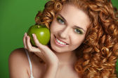 Young happy smiling beautiful woman with apple. Curly hair — Stock Photo