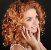 Attractive smiling girl with golden Curly Hair on dark backgroun — Stock Photo