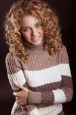 Attractive smiling woman wearing in sweater isolated on black ba — Stock Photo