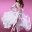 Belly dancer wearing a white costume shaking her hips over pink — Stock Photo #17884323