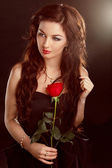Portrait of beautiful brunette woman with red rose — Stock Photo