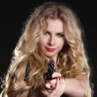 Sexy blond woman holding gun isolated on black background — Stock Photo #18338065