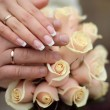 Wedding rings and Hands on roses bouquet - Foto Stock
