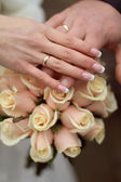 Wedding rings and Hands on wedding bouquet — Stock Photo