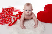 Lovely baby with Valentine's heart and gifts boxes over white — Stock Photo