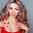 Beautiful woman with wavy hair and red manicure nails on grey ba — Stock Photo