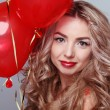 Beautiful young woman with red heart shaped balloons — ストック写真