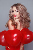 Beautiful young woman with red heart shaped balloons — Stock Photo