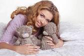 Feliz sonriente joven hermosa con oso de peluche en la cama en h — Foto de Stock