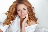 Beautiful happy smiling young woman with curly hair in bed at ho — Stock Photo