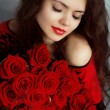 Portrait of attractive Caucasian smiling woman with red roses bo — Stock Photo