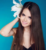 Beautiful woman with long brown hair and white flower. Attractiv — Stock Photo