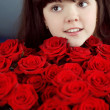 Happy smiling little girl with red roses bouquet flowers — Stock Photo #21289609
