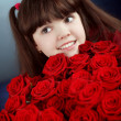 Happy smiling little girl with red roses bouquet flowers — Stock Photo