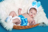 Lying newborn baby on towel over blue background — Stock Photo