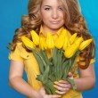 Beautiful Girl With Tulip Flowers over blue. Beauty Model Woman  — Stock Photo