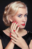 Blond woman with make up and red manicured nails over black, stu — Stock Photo